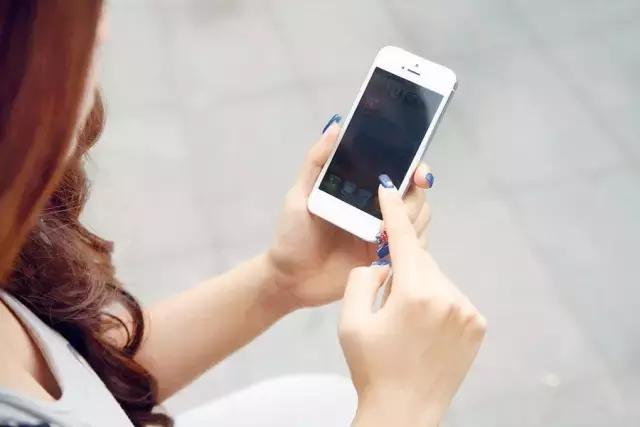 涂着指甲玩手机的女生